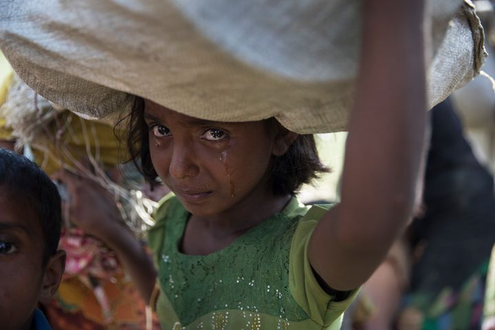 A Rohingya girl cries as refugees fleeing from Myanmar cross a stream in the hot sun on a muddy rice field on October 16, 201