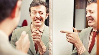 Man pointing at reflection in mirror