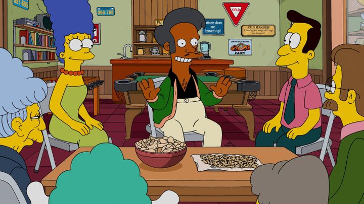 "Apu speaking to Marge and other characters in ""The Simpsons."""