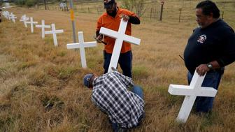 Chris Alcala, Albert Zapata and J.D. erect a line of crosses along the highway on the outskirts of the town where the shooting took place at the First Baptist Church of Sutherland Springs, Texas, U.S., November 11, 2017. REUTERS/Rick Wilking