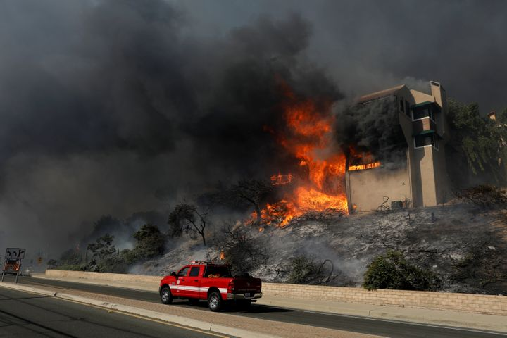 A fire officials drives past a burning home in Ventura, California, on Tuesday.