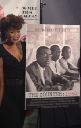 "Director Tracy Twinkie Bryd standing alongside the ""The Counter: 1960"" film poster."