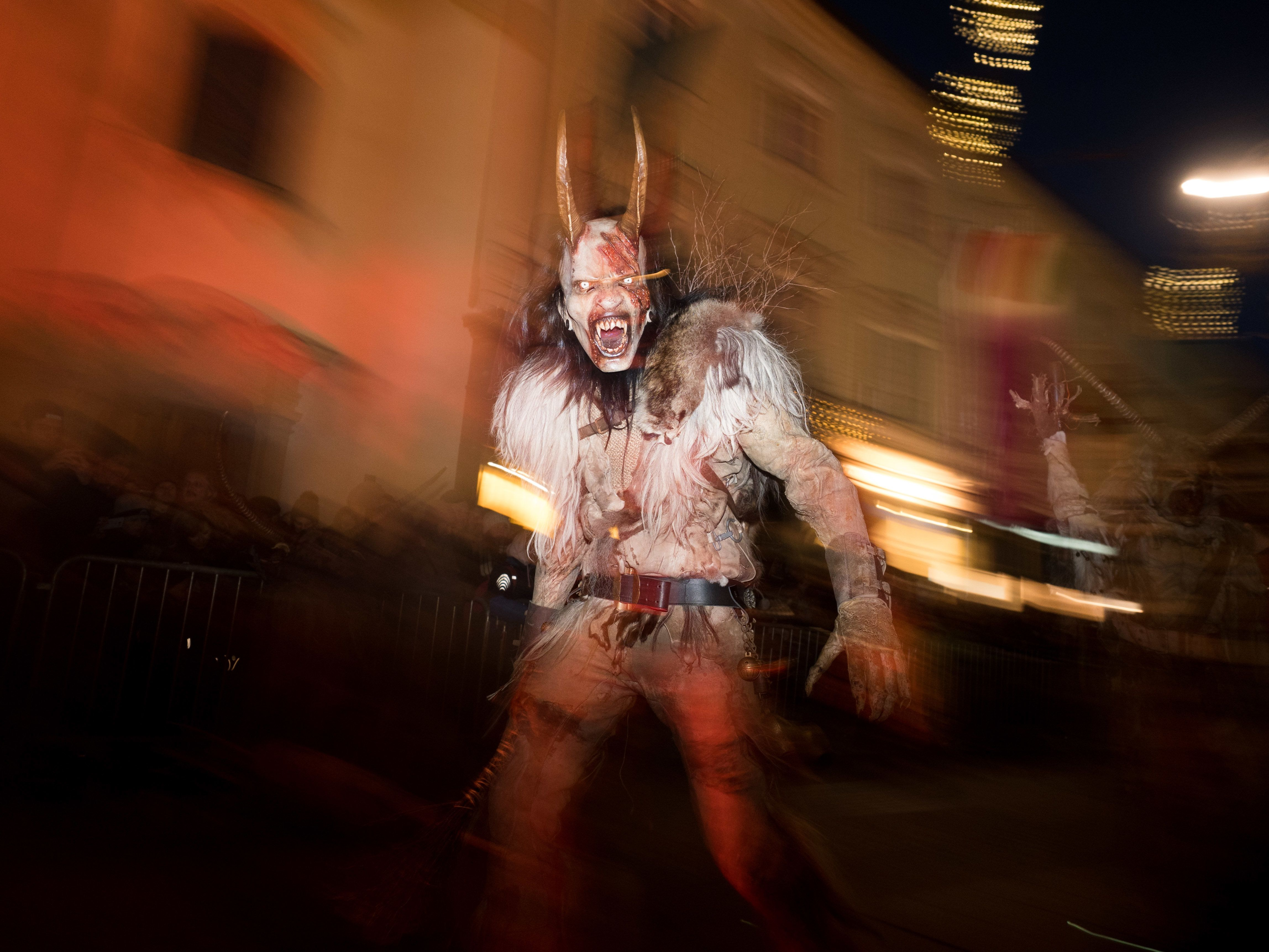 GRAZ, AUSTRIA - 2017/12/03: A devil character seen running in the centre of Graz. Around December 6th, St. Nicolas Day, people dress up as devils run through streets of towns and villages in Austria. They seem like if they jumped out from a horror movie. Or from the hell. They are dressed in animal skins, have horns, strange instruments to scary people. Their faces are turned into nasty grins. They are covered with blood and scars and their long teeth dangle out of their mouths. Special tradition of a devil characters named 'krampus' and 'percht' who are coming with the St. Nicolas to punish bad people was born in remote valleys of Alp mountains hundreds years ago. Long winter nights were full of monsters. But at the end, krampus and percht were not just negative characters. They came to punish everything bad and prepare people for a new start. All the negative things in the village should be forgotten after krampus night. Until now, people dress animal skins and wooden masks to run and scare the audience. They are accompanied by pyrotechnic and light effects and hard music. They keep the tradition clear: no plastic. No Hollywood. Just wooden masks are allowed. Masks cost between 600 to 1200 euro each. Plus horns, animal skin for clothes and special shoes. Some groups come with strange vehicles. They prepare new performance each year. (Photo by Jana Cavojska/SOPA Images/LightRocket via Getty Images)
