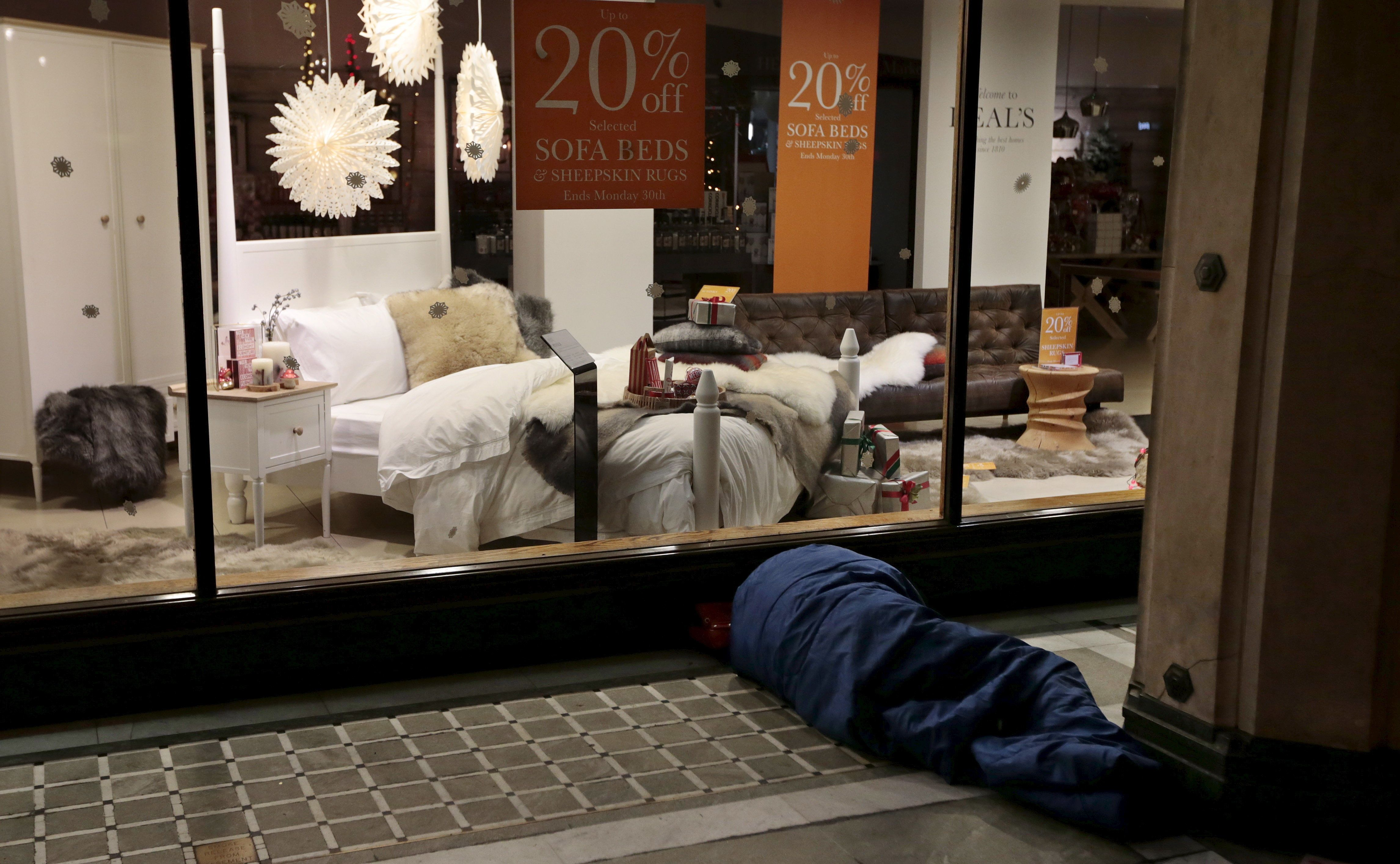 <strong>The number of homeless children in Britain is at a ten year high; a homeless man is pictured sleeping outside a furniture shop in central London</strong>