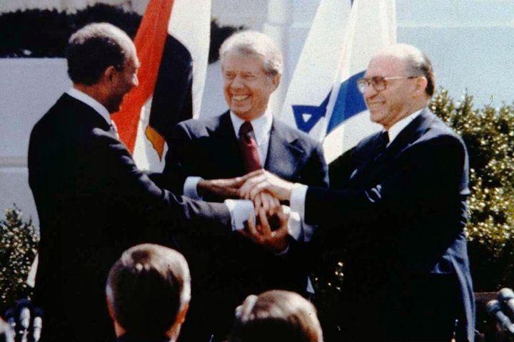 President Jimmy Carter celebrates with Egyptian President Anwar Sadat and Israeli Prime Minister Menachem Begin at the signin