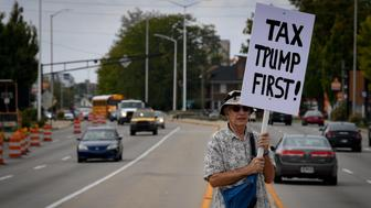 A protester holds a sign during demonstrations as U.S. President Donald Trump delivers a speech on tax reform during an event at the Indiana State Fairgrounds & Event Center Farm Bureau Building in Indianapolis, Indiana, U.S., September 27, 2017.  REUTERS/Bryan Woolston