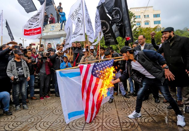 Palestinian protesters burn the US and Israeli flags in Gaza City ahead of Donald Trump's expected decision...