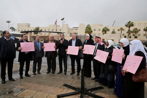 Jordanian members of Parliament hold signs during a sit-in against Trump's decision in front of the U.S. Embassy in Amman, Jo