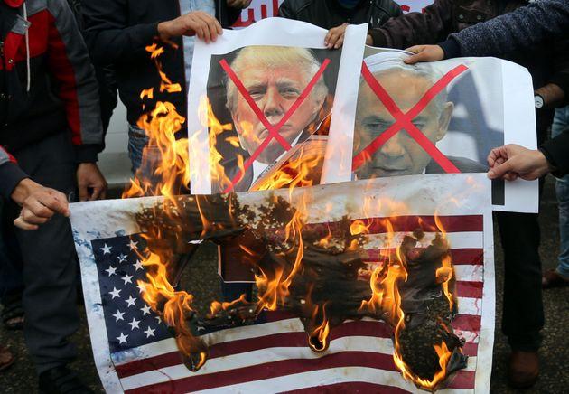 Palestinians burn posters depicting Israeli Prime Minister Benjamin Netanyahu and U.S. President Donald...