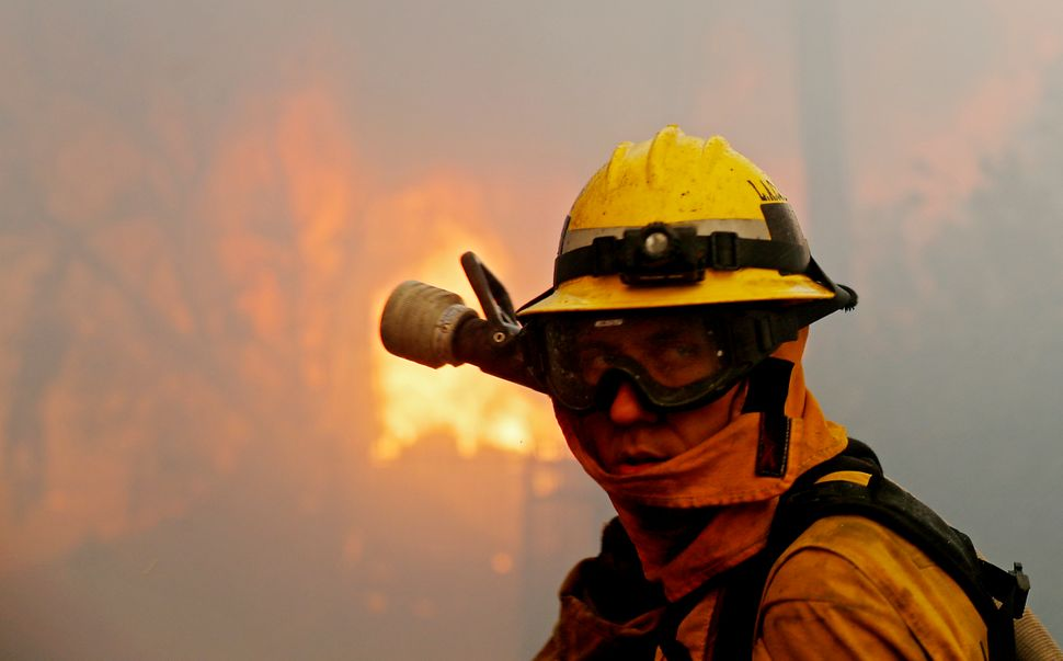 A firefighter gets into position to battle the Creek wildfire as a house is engulfed in flames in Shadow Hills.