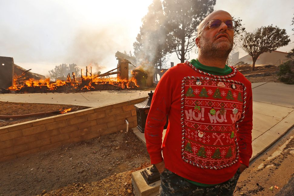 Wearing his Christmas garb, Justin Ekback stands in front of one of the multi-million dollar homes destroyed in Ventura Count