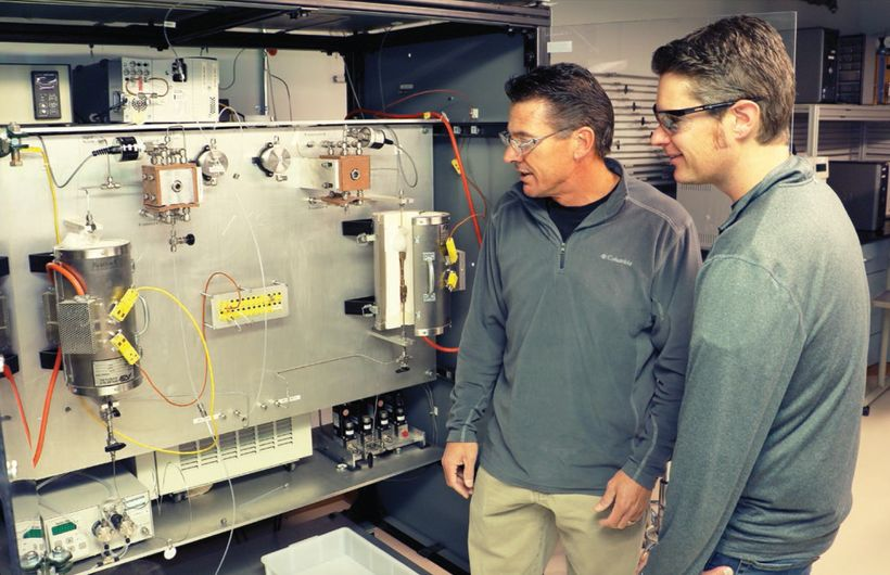 Troy Semelsberger (left) and Andrew Sutton stand alongside the continuous flow reactor developed by their team. This high-thr