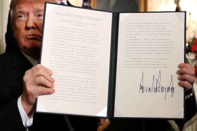 Trump holds up a proclamation that the US government will formally recognise Jerusalem as the capital...