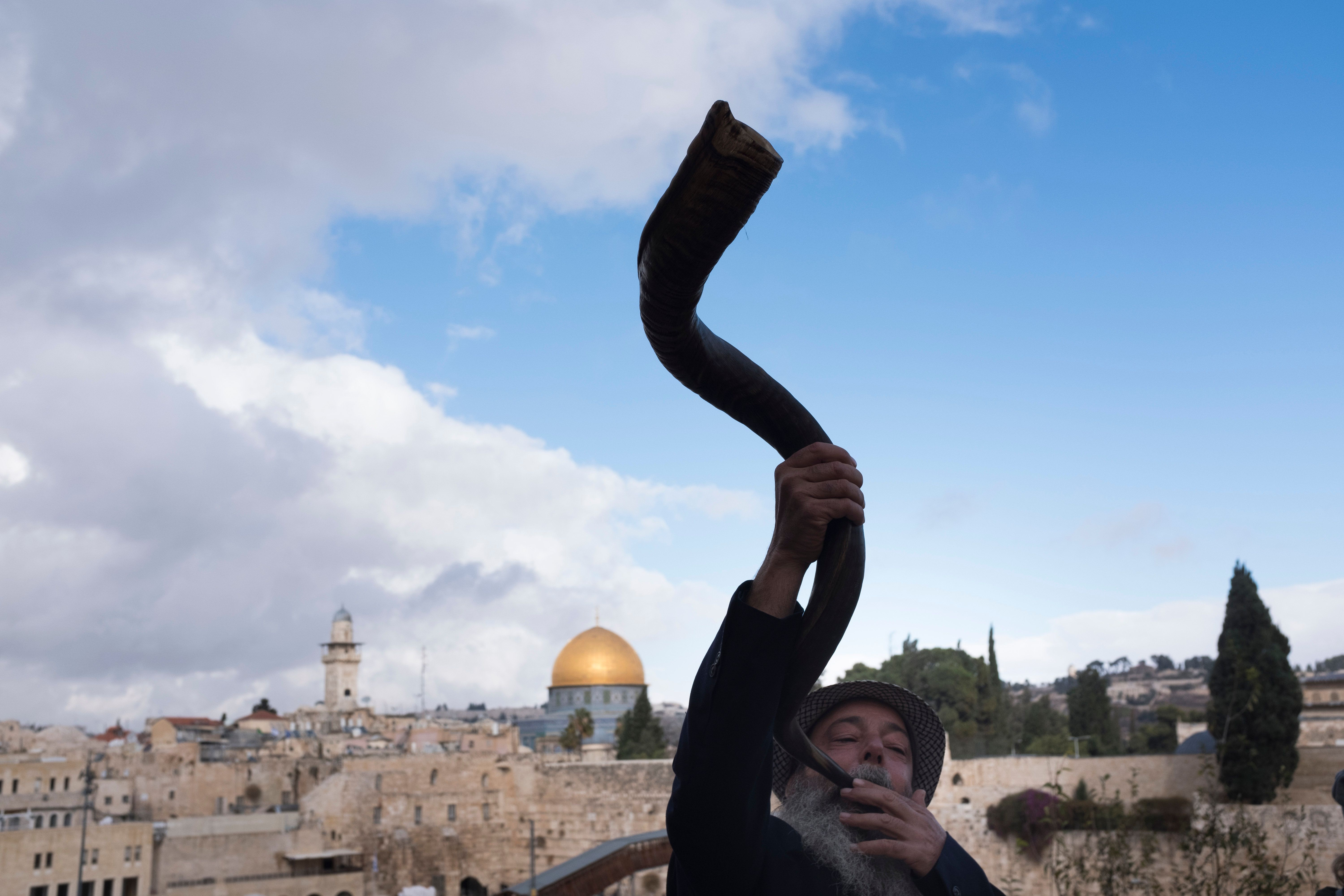 JERUSALEM, ISRAEL - DECEMBER 06: (ISRAEL OUT)  An Ultra Orthodox Jewish man blows the shofar (ram's horn) with the golden Dome of the Rock Islamic shrine behind on December 6, 2017 in Jerusalem, Israel. U.S. President Donald Trump will announce his recognition of Jerusalem as Israel's capital on Wednesday.