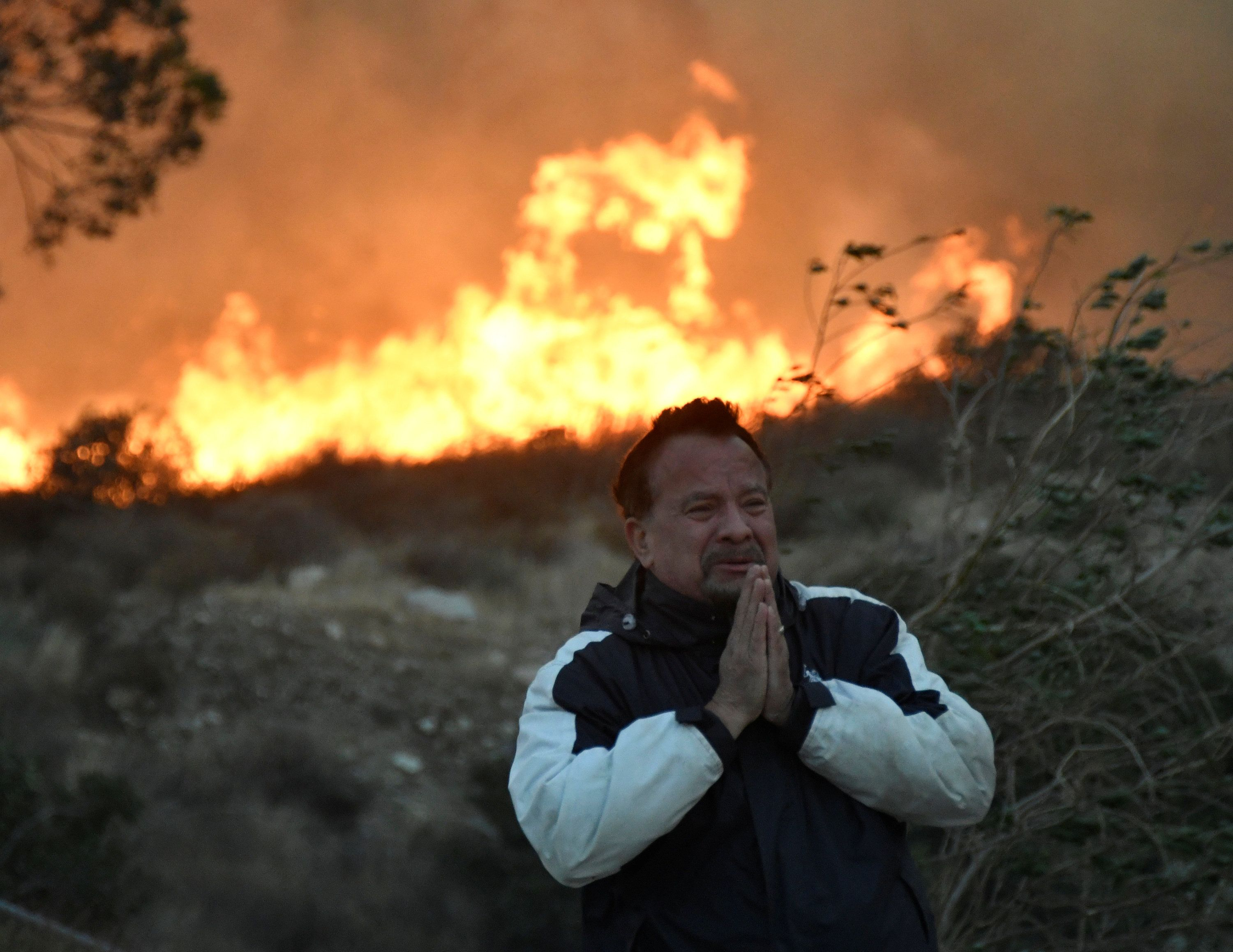 A man prays as the Creek fire advances behind him in the San Fernando Valley area of Los
