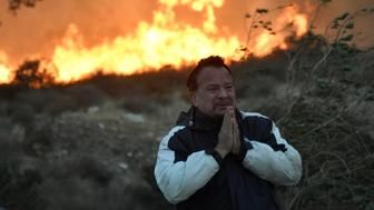 A local man tries to cope and prays during an early-morning Creek Fire that broke out in the Kagel Canyon area in the San Fernando Valley north of Los Angeles, in Sylmar, California, U.S., December 5, 2017.   REUTERS/Gene Blevins