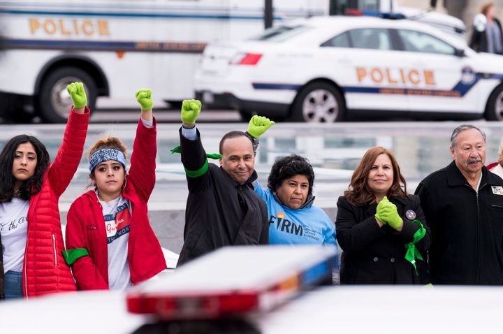 Immigration protesters, including Rep. Luis Gutiérrez (center), stand in a line after being arrested at the U.S. Capitol on Dec. 6.
