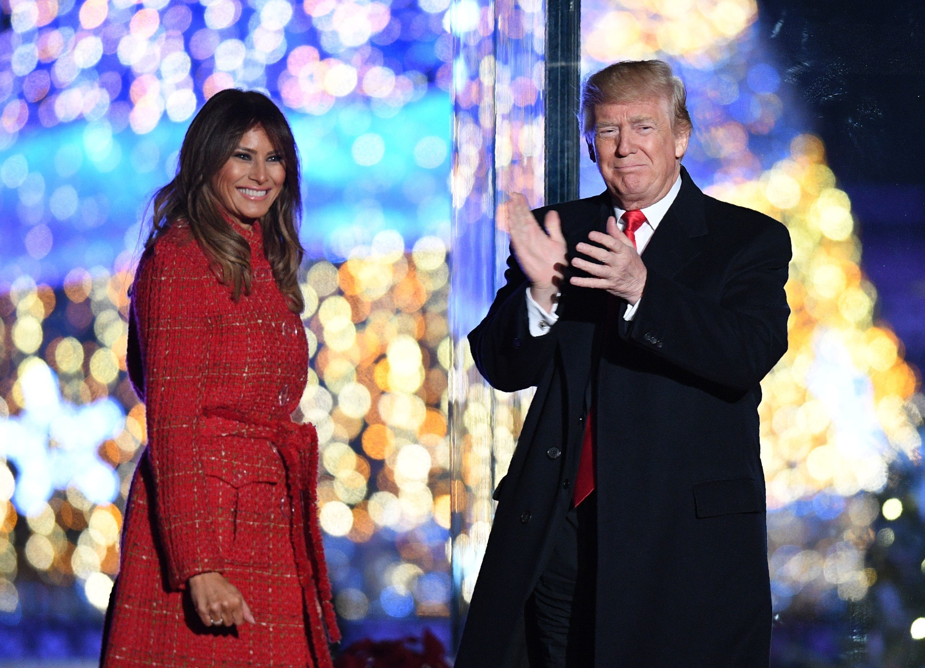 US President Donald Trump (R) gestures as First Lady Melania Trump smiles during the 95th annual National Christmas Tree Lighting ceremony at the Ellipse in President's Park near the White House in Washington, DC on November 30, 2017. / AFP PHOTO / JIM WATSON        (Photo credit should read JIM WATSON/AFP/Getty Images)
