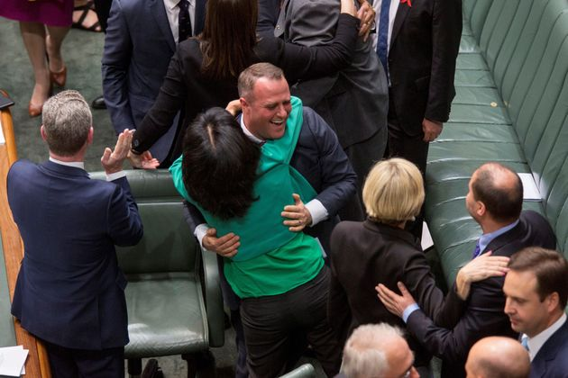 Members of Parliament embrace one another after parliament passed the same-sex marriage bill in the Federal...