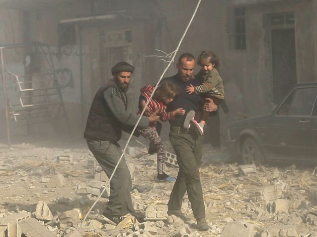 Nearly one in four civilians killed in Syria is a child, a report has found; Syrian men are seen carrying...