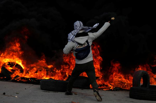 A Palestinian protester hurls stones towards Israeli troops during clashes near the Jewish settlement of Beit El, near the We