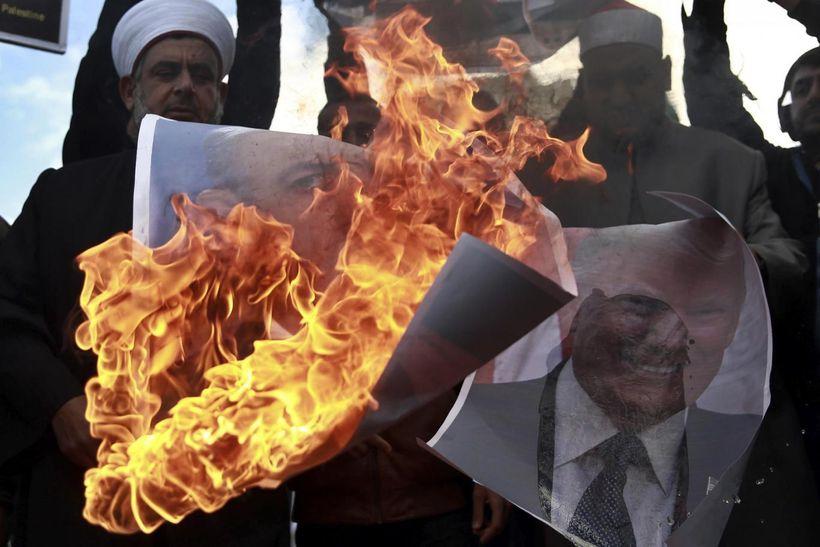 Palestinians burn posters of Israeli Prime Minister Benjamin Netanyahu and U.S. President Donald Trump, during a protest aga
