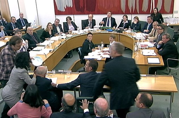 Rupert Murdoch gets pied in the face during a Commons select