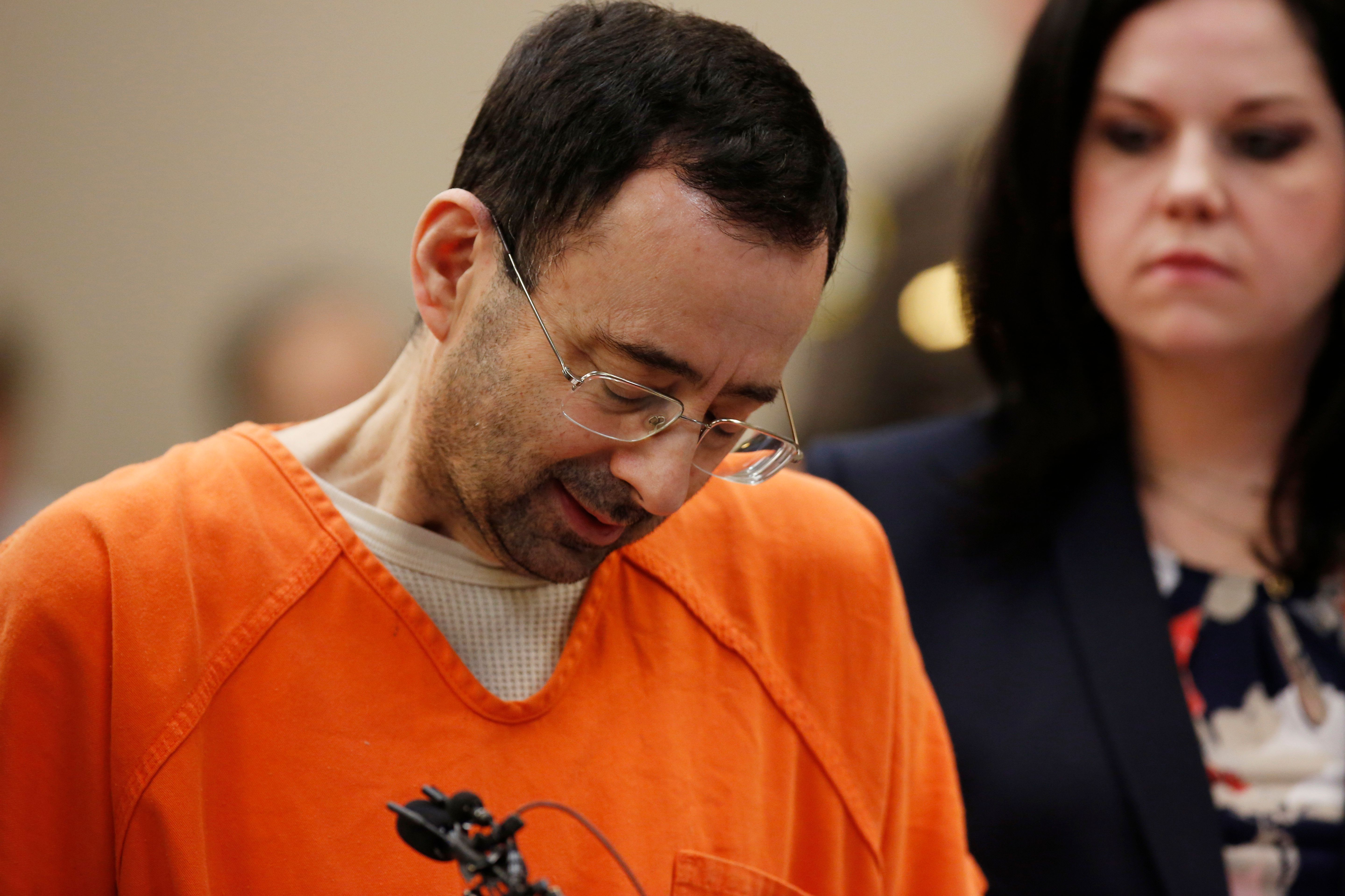 Former Michigan State University and USA Gymnastics doctor Larry Nassar (L) reacts to defense attorney Shannon Smith (R) reading the charges he pled to in Ingham County Circuit Court on November 22, 2017 in Lansing, Michigan. Former USA Gymnastics team doctor Lawrence (Larry) Nassar, accused of molesting dozens of female athletes over several decades, on Wednesday pleaded guilty to multiple counts of criminal sexual conduct. Nassar -- who was involved with USA Gymnastics for nearly three decades and worked with the country's gymnasts at four separate Olympic Games -- could face at least 25 years in prison on the charges brought in Michigan.  / AFP PHOTO / JEFF KOWALSKY        (Photo credit should read JEFF KOWALSKY/AFP/Getty Images)