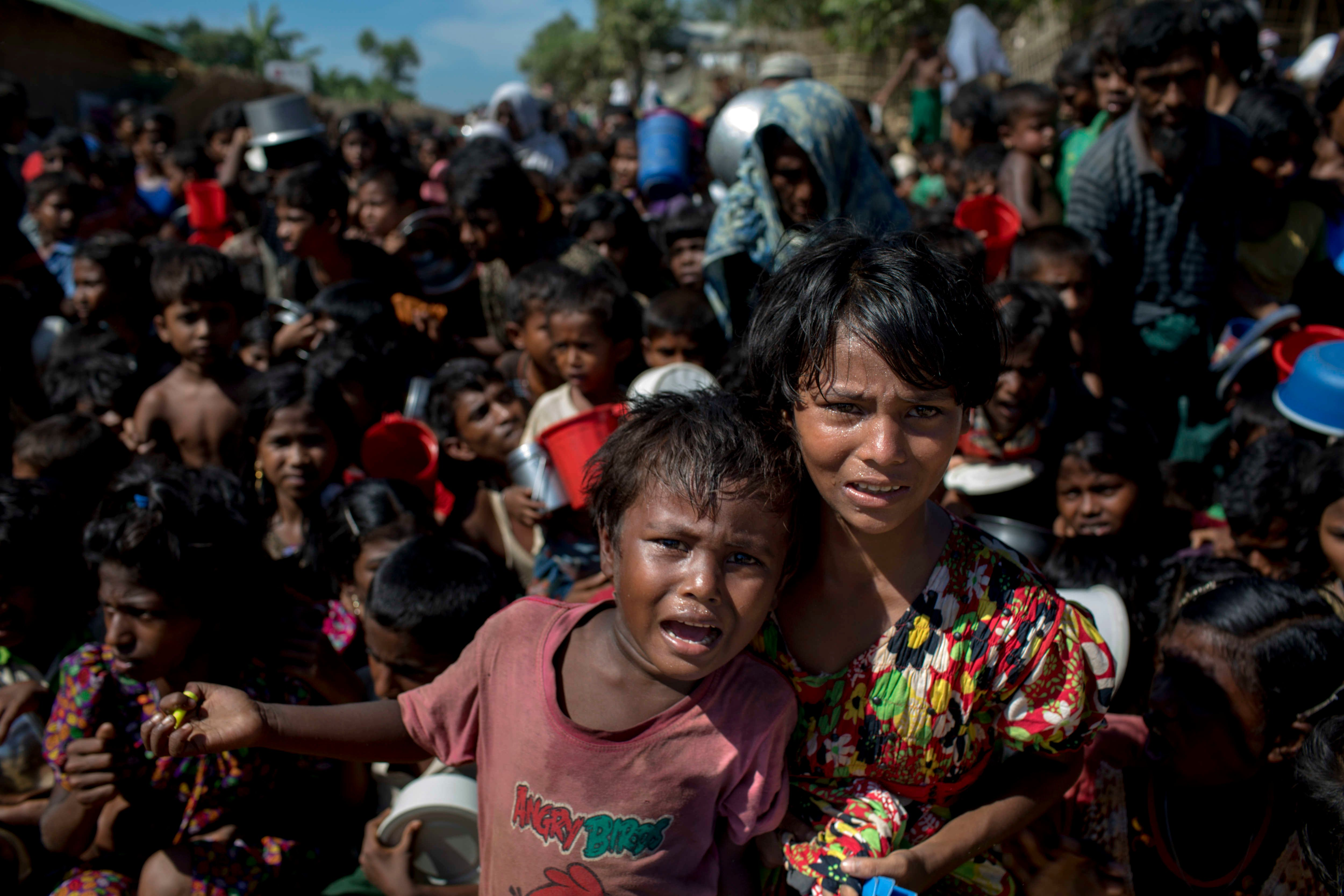 Rohingya refugee children wait in front of a food distribution center in a refugee camp in Bangladesh.