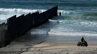 A U.S. Customs and Border patrol agent patrols the beach on an all-terrain vehicle next to the Mexico- U.S. border wall where it enters the Pacific Ocean at Border Field State Park in San Diego, California, U.S., November 18, 2017.      REUTERS/Mike Blake