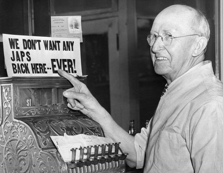A barber points to his own anti-Japanese sign after Japanese-Americans were incarcerated during World War II.