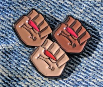 GRL TRBL's Solidarity Fist pin.