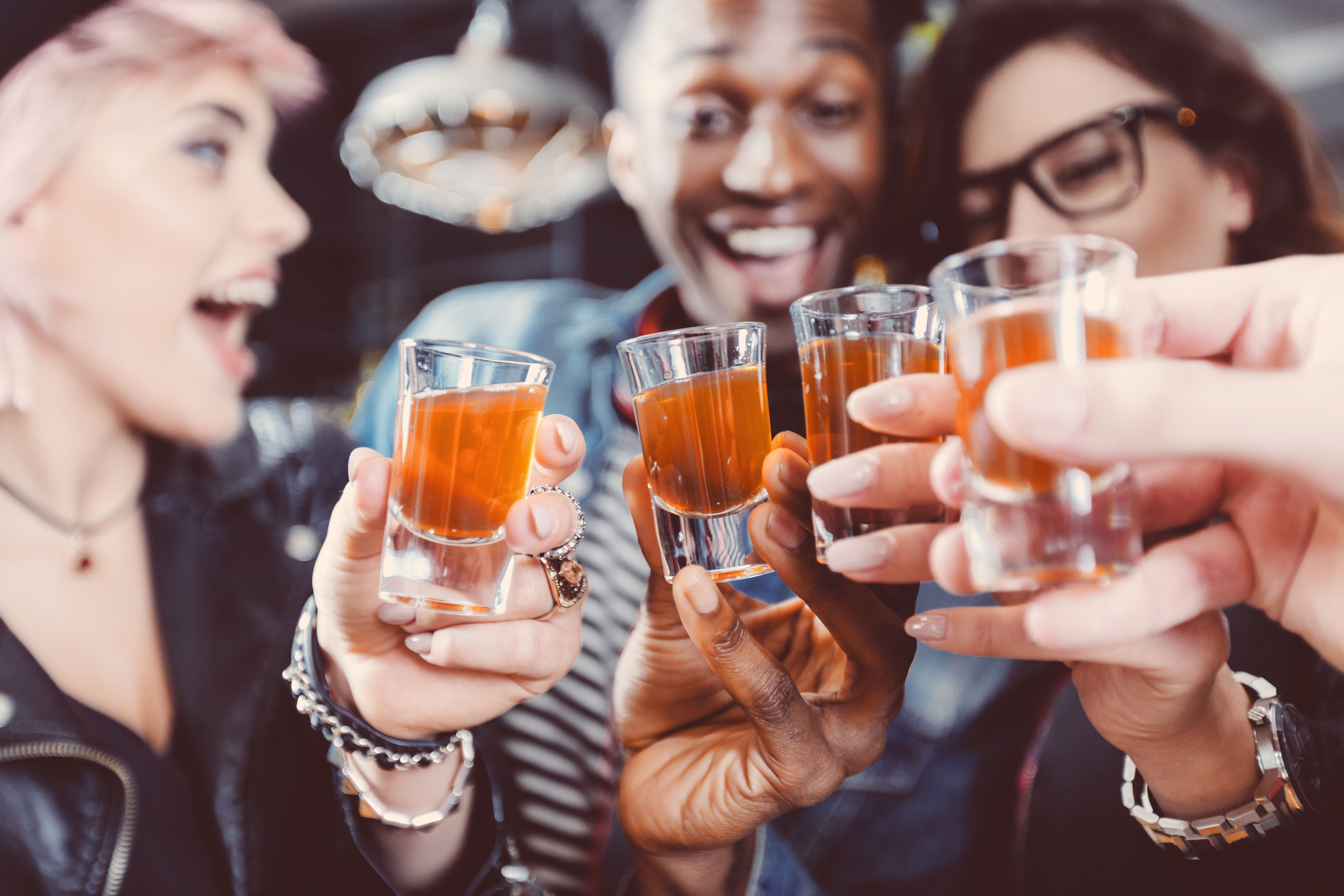 Multi ethnic group of happy friends - caucasian and afro american - drinking shots in the pub. Focus on hands and shot glasses.