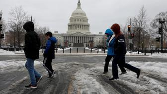 People walk through the snow outside the Capitol Building in Washington, D.C., U.S. March 14, 2017.  REUTERS/Aaron P. Bernstein