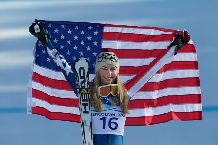 Lindsey Vonn holds up the flag after winning gold in the women's downhill competition at the 2010 Winter Olympics, Feb. 17, 2