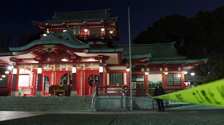 A policeman stands guard in front of the main temple of the Tomioka Hachimangu shrine in Tokyo, Japan in this photo tak