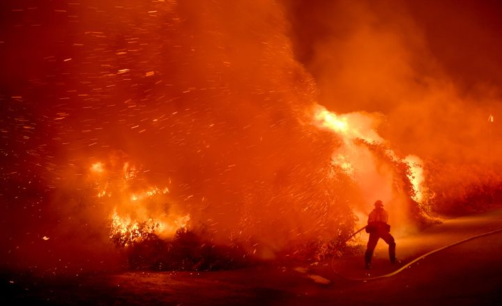 A firefighter battles the Thomas fire in the town of La Conchita early Thursday morning.