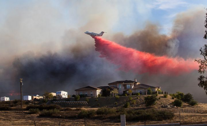 A plane drops fire retardant to stop the wind-driven Liberty fire near Los Alamos Road on Dec. 7, 2017, in Murrieta.