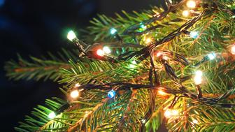 Christmas lights on Christmas tree, decorative garland in dark space