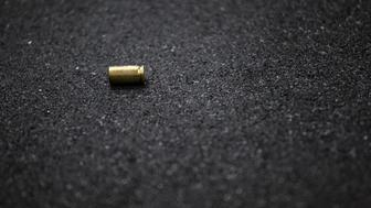 Cases of bullets lying on the floor of asphalt