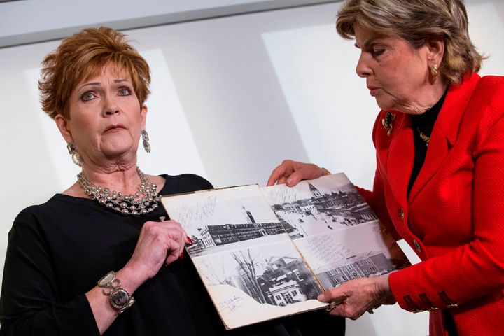 Attorney Gloria Allred (right) and Beverly Young Nelson hold up Nelson's high school yearbook at a press conference in Novemb