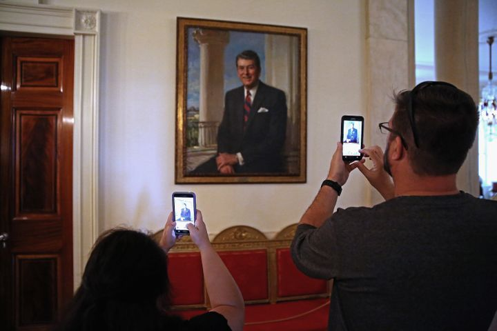 Visitors photograph former President Ronald Reagan's portrait during a tour of the White House. July 1, 2015.