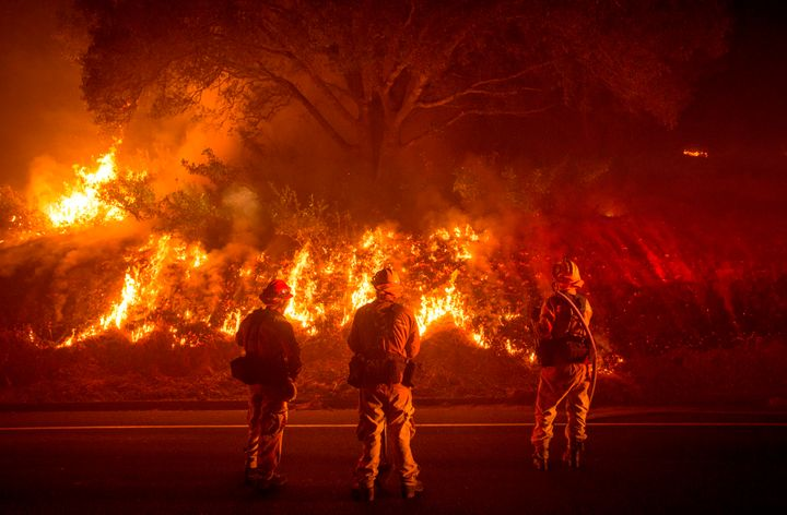 Firefighters monitor flames on the side of a road as the Detwiler fire rages on near the town of Mariposa, California, on Jul
