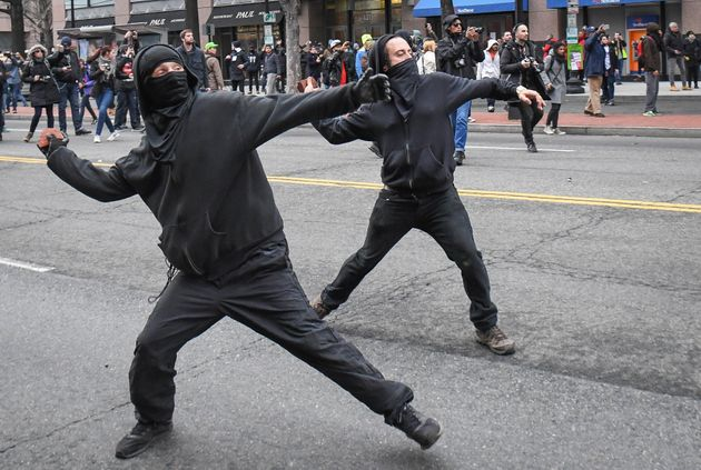 Protesters throw rocks at police during a protest near the inauguration