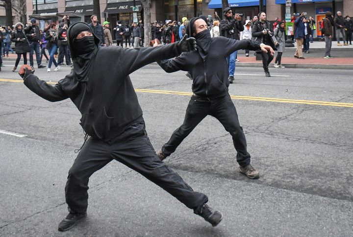 Protesters throw rocks at police during a protest near the inauguration site.