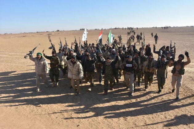 Members of the Hashed al-Shaabi paramiliatries celebrate after Iraq's Prime Minister declared victory...