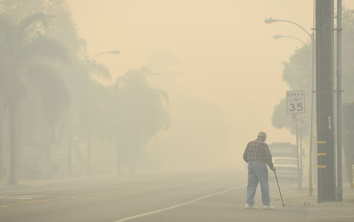 A man walks along Ventura Avenue as the Thomas fire leaves behind smoke on Dec. 8.