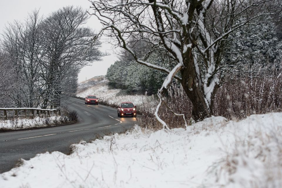 Cars travel on a cleared road near Diggle, Greater Manchester, on