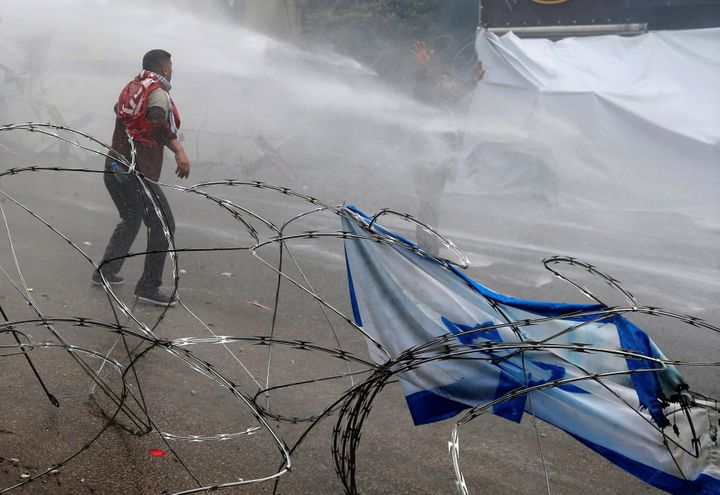 Protesters are sprayed with water near the U.S. embassy in Awkar, north of Beirut, Lebanon on December 10, 2017. (REUTERS/Moh
