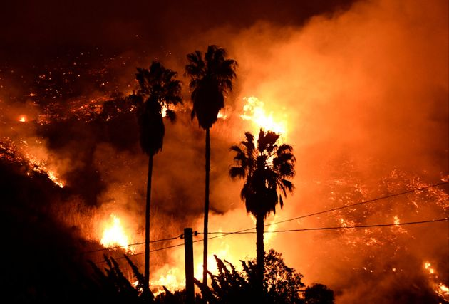 Flames spread in a valley from a Santa Ana wind-driven brush fire called the Thomas fire near Ventura,...